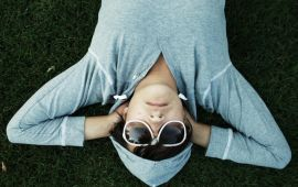 woman in gray hoodie and sunglasses asleep on grass