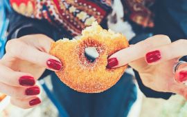 Woman's hand with nail polish holding partially eaten sugar donut.