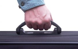 close up of man's hand on luggage handle