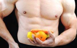 Shirtless male torso and hand holding fruit and vegetables