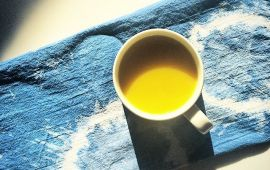 Mug of turmeric tea sitting on denim cloth.