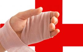 Close up of hand in bandage in front of red cross symbol.