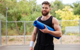 Bearded man outdoors holding rolled yoga mat