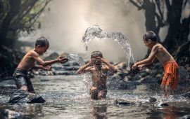 3 boys playing and splashing in water