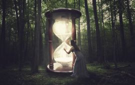 Woman in forest peering into huge hourglass