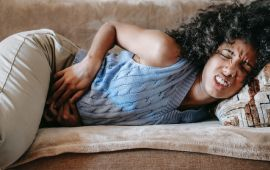 Woman laying on couch cringing and holding her stomach