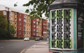 Poster on utility pole says repeatedly WE ARE ONE
