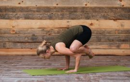 Woman doing yoga crow pose in front of wooden wall