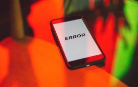 Celular phone on bright orange background with large ERROR message