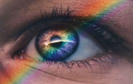 Close up on an eye with a rainbow prism reflection across it.