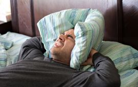 Man who can't sleep squeezing pillow around his head.