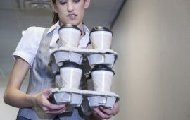 Woman carefully balancing stacked trays of coffee cups.