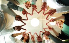 Many people gathered in a circle making peace sign symbol with fingers surrounding a light like the sun
