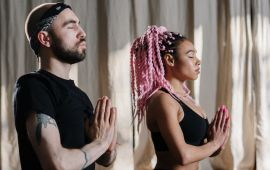 Man and woman in prayer pose, meditating