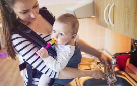 Mother with baby in carrier washing dishes doing chores