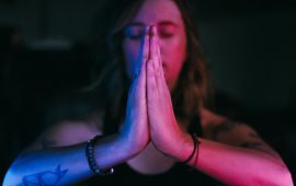Close up of prayer pose namaste hands lit in blue and pink
