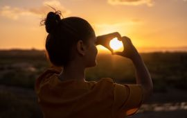 Silhouette of woman holding up hands in shape of a heart framing the sun at dusk.