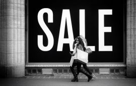 black and white image of women with shopping bags in front of sign SALE