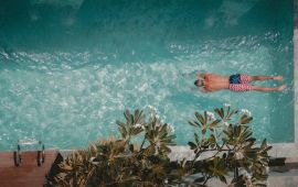 Overhead view of man diving into swimming pool.
